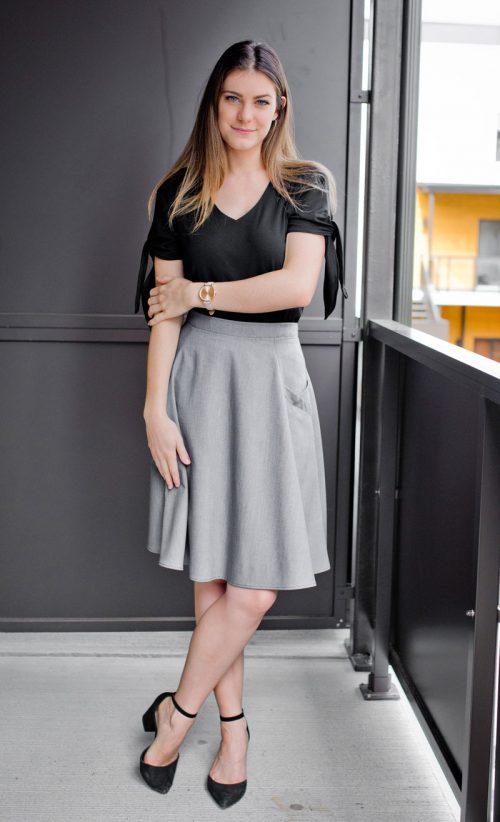 look chandail noir avec boucles sur les manches et jupe grise circulaire avec poches
